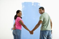 Couple next to half-painted wall. Stock Photos