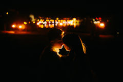 Couple at the night city. Beautiful couple kissing on the background of the city at night Stock Image