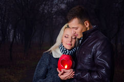 Couple in the night with lantern. Couple hugging in the park at night, holding in hands lantern heart Royalty Free Stock Images