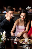 Couple night out. Glamourous young couple eating ice-cream, drinking coffee Royalty Free Stock Images