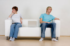 Couple not talking. A young teen couple sitting on opposite ends of a sofa, not talking and ignoring each other. Theme: non-communication royalty free stock image