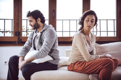 Couple not talking after a fight on the sofa in living room at home Stock Images