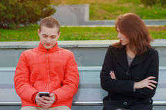 Couple not talking to each other typing on mobile phones. Sad girl Stock Photography