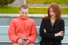 Couple not talking to each other typing on mobile phones. Sad girl Royalty Free Stock Photography