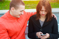 Couple not talking to each other typing on mobile phones. Sad girl Stock Photos