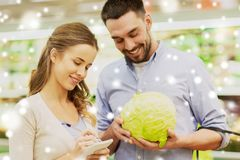 Couple with notebook and cabbage at grocery store Stock Photos