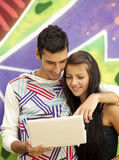 Couple with notebook near graffiti wall. Stock Image