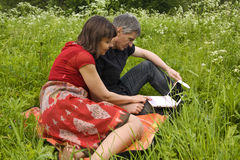 Couple with notebook in park Stock Photo