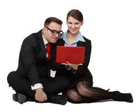 Couple on Notebook. Young business couple looking together to the notebook while sitting against a white background Stock Image