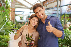 Couple in nursery shop holding thumbs up. Happy couple in nursery shop holding their thumbs up royalty free stock images