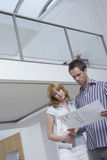 Couple Observing Plan In New Home Royalty Free Stock Image