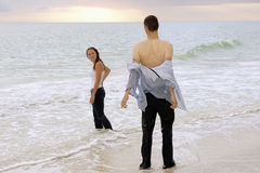 Couple at ocean at sunset. A soaked fully clothed couple are at the water's edge at the beach, the man is taking off his shirt Stock Image