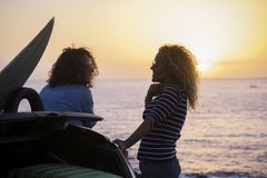 Free Couple Of Beauty Women In Vacation Enjoy The Friendship In Front Of A Colured Sunset With Ocean Horizon - Travel And Lifestyle Stock Images - 142875654