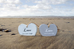 Couple Of Inscribed Wooden Love Hearts In The Sand Stock Photos