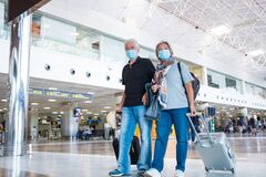 Free Couple Of Seniors And Mature People Walking In A Airport With Their Luggage And Trolleys - Vacations And Traveling In Covid-19 And Stock Images - 193880294