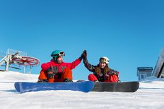 Couple Of Snowboarders Gives High Five To Each Other Royalty Free Stock Photos