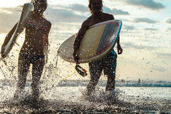 Couple Of Surfers At Sunset Stock Photos