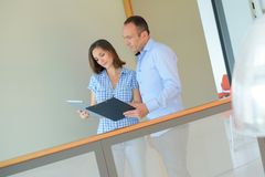 Couple in office corridor looking at clipboard. Man Royalty Free Stock Photo