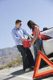 Couple With Oil Can Standing By Car Stock Photos