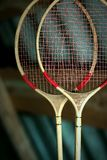 A couple of old badminton rackets hanging in the attic. stock photos