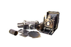 Couple of old cameras. A very old camera (from the beginning of the XXth century) set with another old camera (from the fifties) and old film and negatives royalty free stock photos