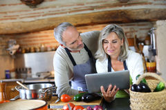 Couple in old kitchen looking for recipe on internet Stock Image