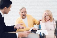 A couple of old people came to see a realtor. The old man and the woman are very upset. A couple of old people came to see a realtor. The old men and the women stock photo