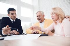 A couple of old people came to see a realtor. The realtor explains something to the old man and the woman. A couple of old people came to see a realtor. The Stock Photography