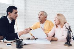 A couple of old people came to see a realtor. The realtor explains something to the old man and the woman. A couple of old people came to see a realtor. The Royalty Free Stock Photography