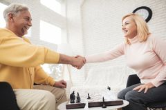A couple of old people play chess at home. They play with delight and joy. They are sitting in their living room by the big window Royalty Free Stock Photos