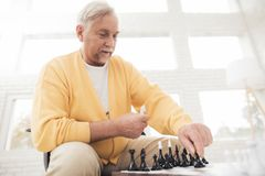 A couple of old people play chess at home. They play with delight and joy. They are sitting in their living room by the big window Royalty Free Stock Photography