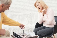 A couple of old people play chess at home. They play with delight and joy. They are sitting in their living room by the big window Royalty Free Stock Photo