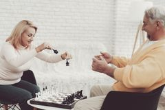Couple of Old People Playing Chess at Home. stock photos