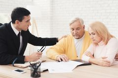 A couple of old people at a reception with a realtor. The old people are upset. Royalty Free Stock Photography