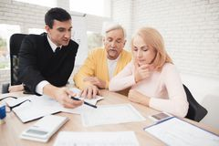 A couple of old people at a reception with a realtor. They are satisfied with the service. The realtor in a black suit is sitting next to him. They together stock photos