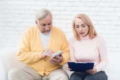 A couple of old people are sitting on the couch and are concentrating something. A men has a yellow cardigan, a pink sweater on a woman. They have documents Royalty Free Stock Photography