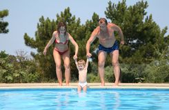 Couple omit child in pool Stock Photos