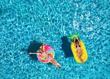 Free Couple On Inflatable Floats Over Blue Pool Water Stock Photography - 160130152