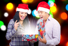 Couple open a magic Christmas gift. Surprised happy couple opens a magic Christmas gift with lights royalty free stock photography