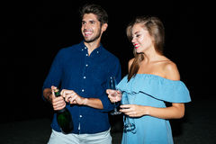 Couple opening bottle of champagne on the beach at night. Happy young couple opening bottle of champagne on the beach at night stock image