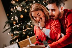 couple opening christmas presents sitting in cozy living room with christmas tree background royalty free stock photography