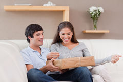 Couple opening parcel on the sofa Royalty Free Stock Image