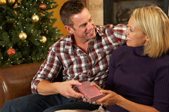 Couple Opening Presents In Front Of Christmas Tree Royalty Free Stock Photography