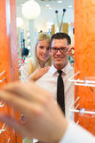Couple in optician's shop trying spectacle frame Stock Photography