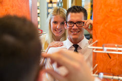 Couple in optician's shop trying spectacle frame Royalty Free Stock Photos