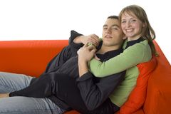 Couple on the orange couch. Royalty Free Stock Photos
