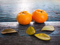Couple Orange fruits. And leaves on bench, old wood background Royalty Free Stock Images