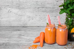 A couple of orange smoothie drinks in huge mason jars. Detox beverages with ripe cut carrot and green plant on a gray Royalty Free Stock Images