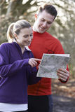 Couple Orienteering In Woodlands With Map And Compass Royalty Free Stock Images
