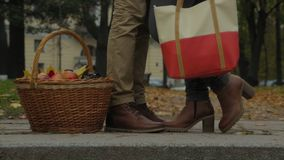 Couple in outdoor with picnic basket, kissing. Woman raises her leg. Man and woman standing outdoors or in the park and. Woman raise her leg. Kissing HD Royalty Free Stock Photos
